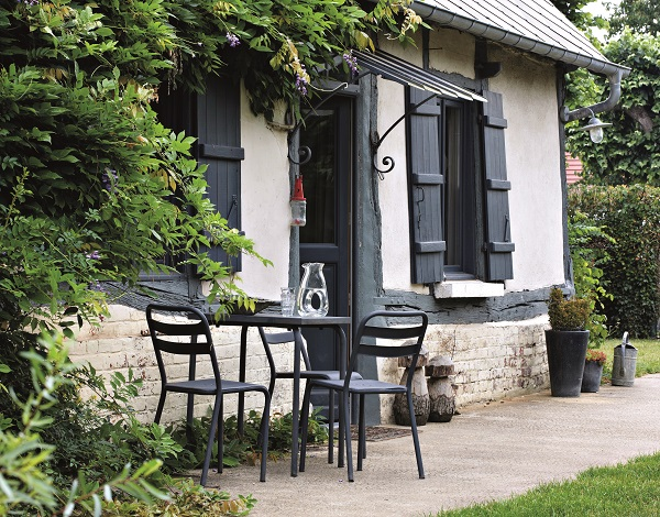 In front of the wisteria-covered old farmhouse are metal chairs and a round table from the 1950s.