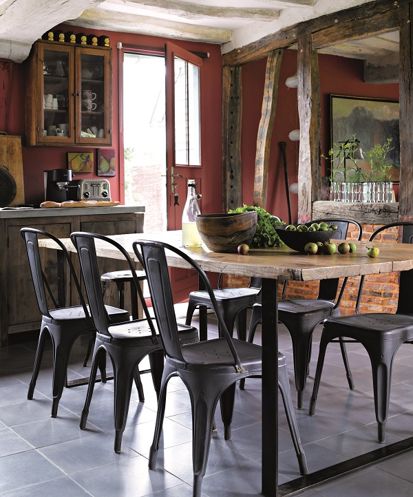 On the other side of the now opened room, divided by beams,the kitchen is dominated by a vintage table used for food preparation and eating, with vintage metal chairs from the 1950s on either side. The glazed kitchen door leads out into the garden and the summer dining room.