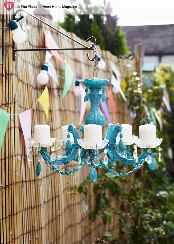 An old plastic chandelier, stripped of its wiring, creates a quirky, mood-setting outdoor light. Spray-painted a vibrant blue and with pillar candles added where light bulb fittings once were, it is hung from a hanging basket bracket screwed into a fence post.