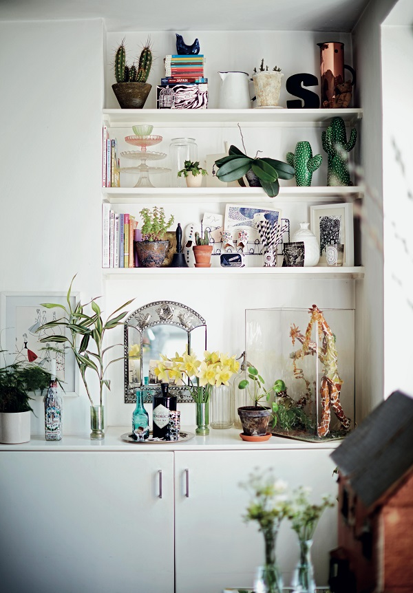 Open shelving in both the living room and kitchen allows the couple's style to shine through. The fireplace shelves display decorative items like small plants, pictures and books, while the cupboards beneath serve as a drinks cabinet and storage for extra glassware, candles, vases and other things they'd rather not have on show.