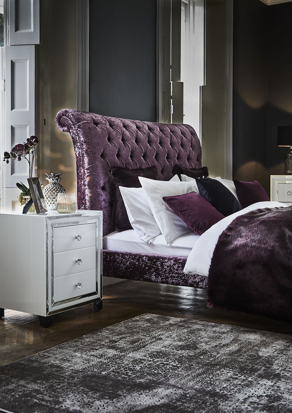 Plush Deco - Odeon Bed £1175, Krystal 3 Drawer Bedside £355, Silver Ceramic Pineapple Table Lamp £35, Aubergine Faux Fur Throw £199.