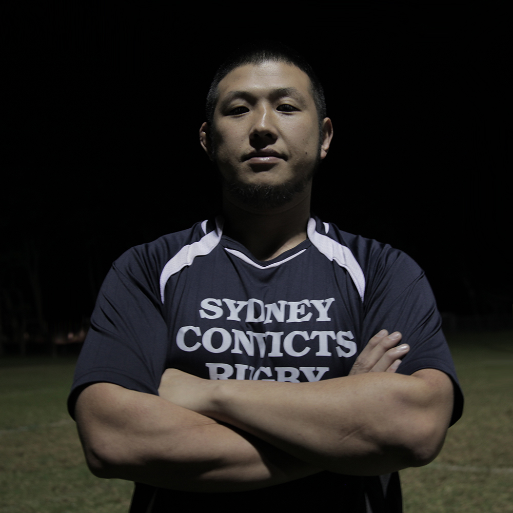 Aki Mizutani /  Sydney Convicts     1st XV forward   When Aki Mizutani came out to his family in Japan they simply said no. So what did he do? He typed 'rugby + gay' into Google. The Sydney Convicts Rugby Club popped up top of the list. Despite his patchy English, Aki didn't muck around. He booked himself a one-way plane ticket to Sydney, stepped off the plane on a Wednesday, joined training on a Thursday, then played his first game of rugby with the Convicts on a Saturday. He's a big guy in Japan and easily makes the scrum but here in Australia, it's not that easy, compared to the other blokes, he's small. But Aki is determined to wear the number 1 jersey and fill the position that is loose head prop.