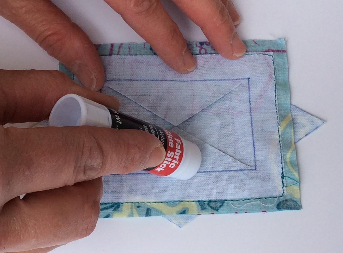 I put the glue at the base of the triangle near the fold line.
