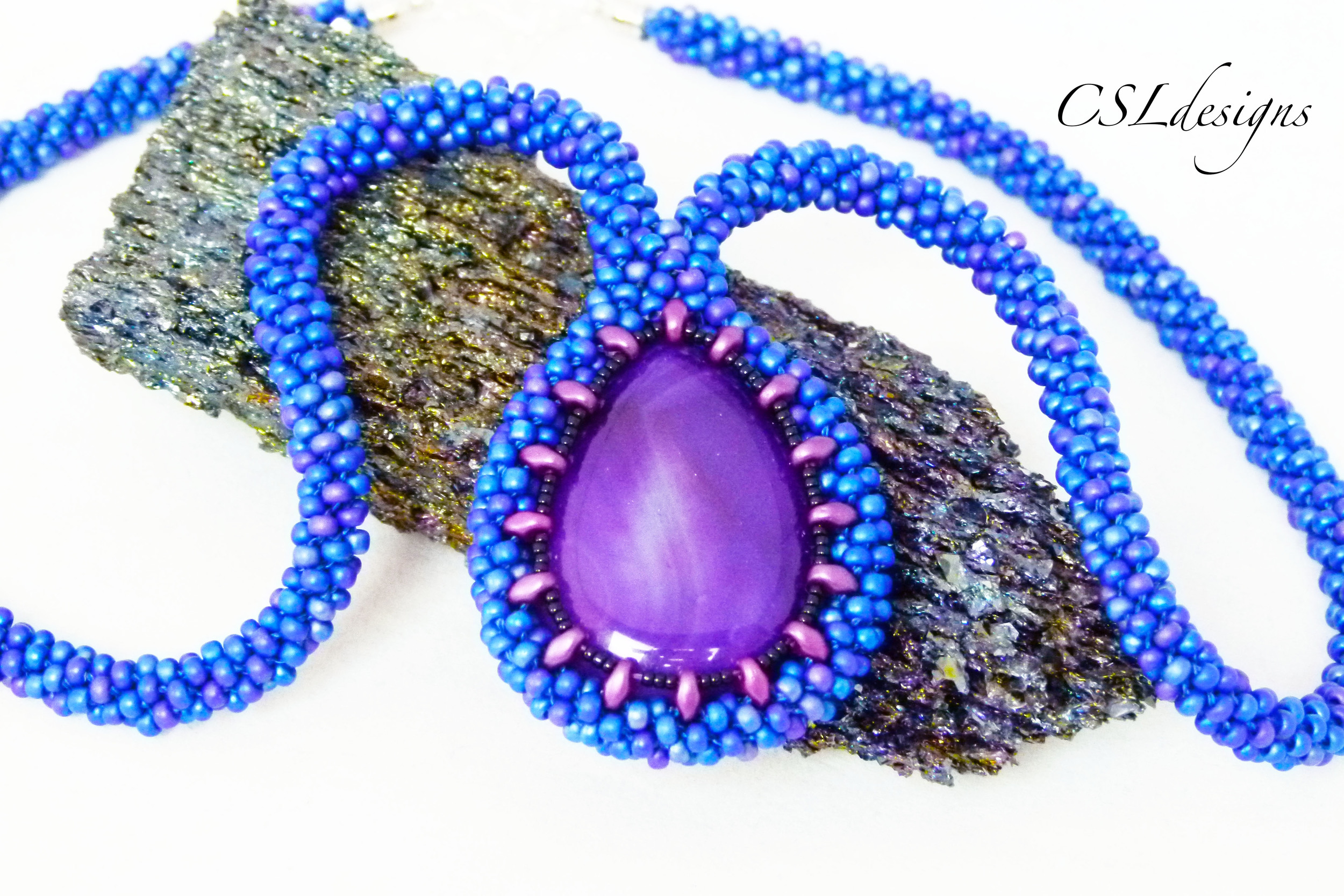 Beaded kumihimo cabochon with SuperDuos purple stone close.jpg