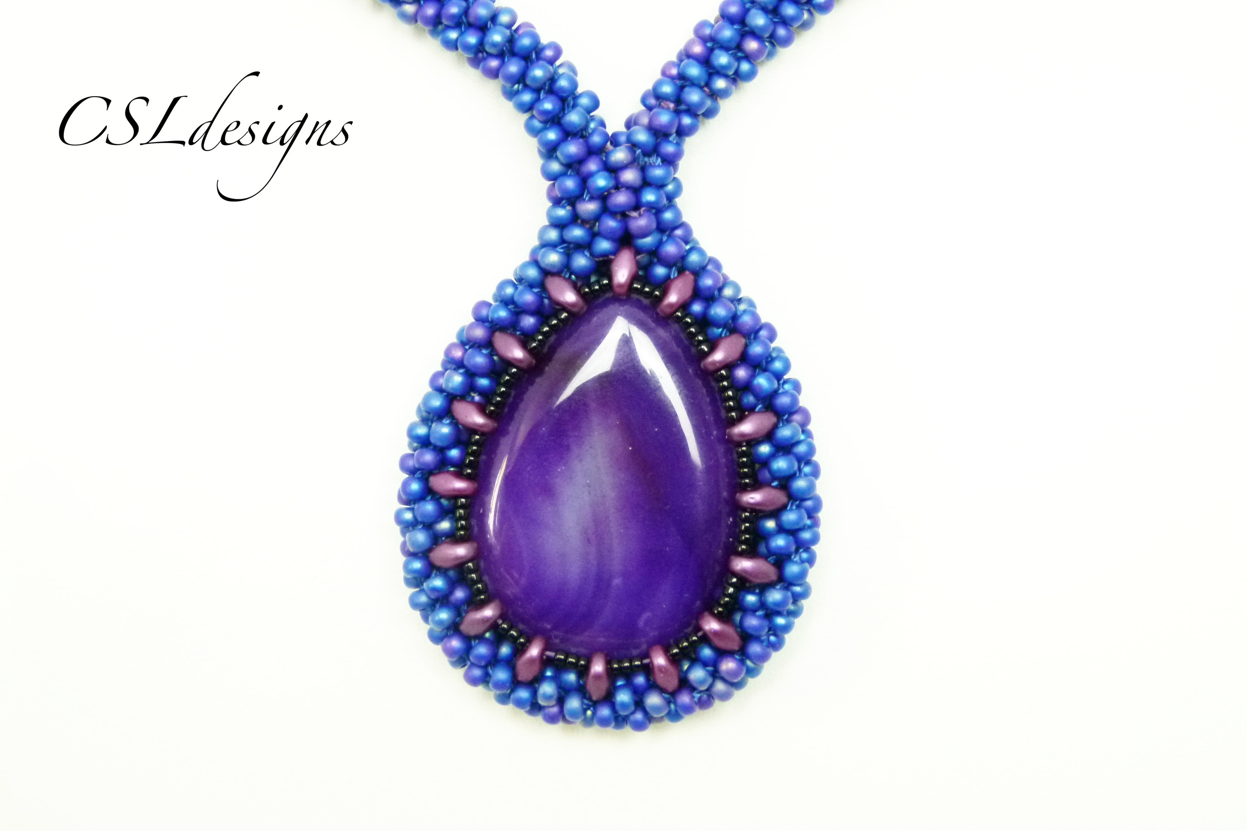 Beaded kumihimo cabochon with SuperDuos purple stand front close.jpg