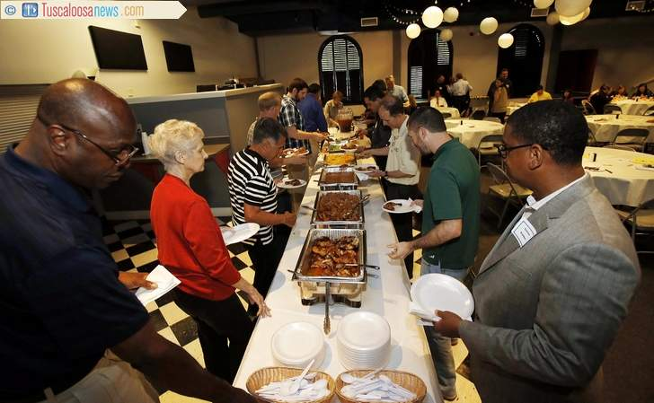 Guests make their plates during a luncheon at Calvary Baptist Church with Eric Boykin to promote the Hope Initiative Ministry in Tuscaloosa, Ala. on Thursday April 16, 2015