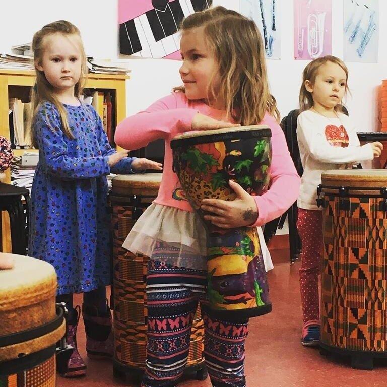 A kindergarten student improvises a drum beat.
