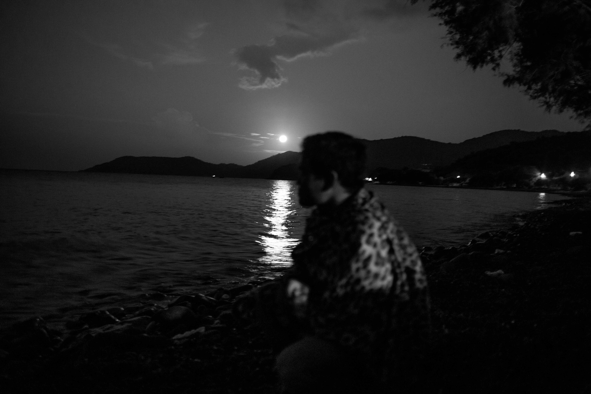 "An Afghan looks out towards the twinkling lights of the Turkish coast from which he has left. In the background, the ""super moon"" rises casting a silhouette."