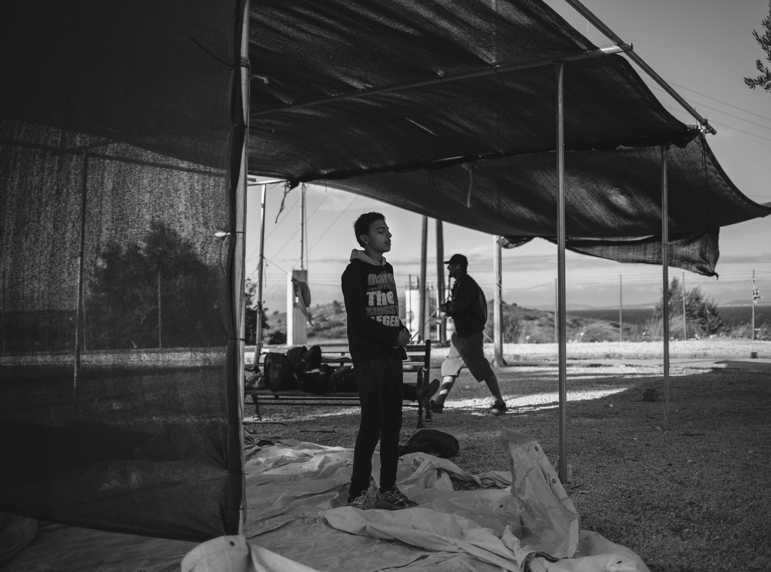 Performing midday prayers at Kara Tepe camp.