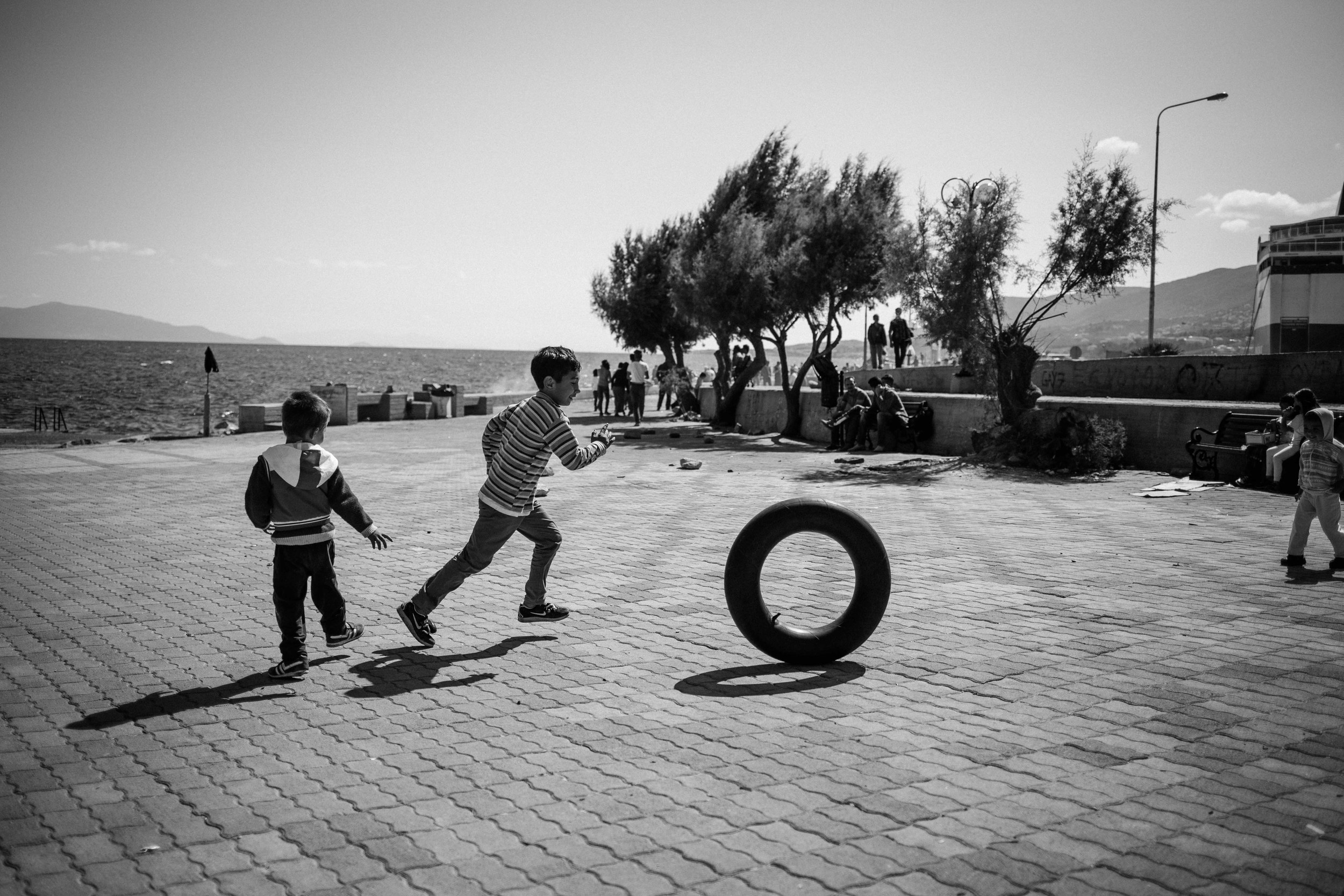 A young Syrian, Afghan and Iranian child play in Mytilene Port.