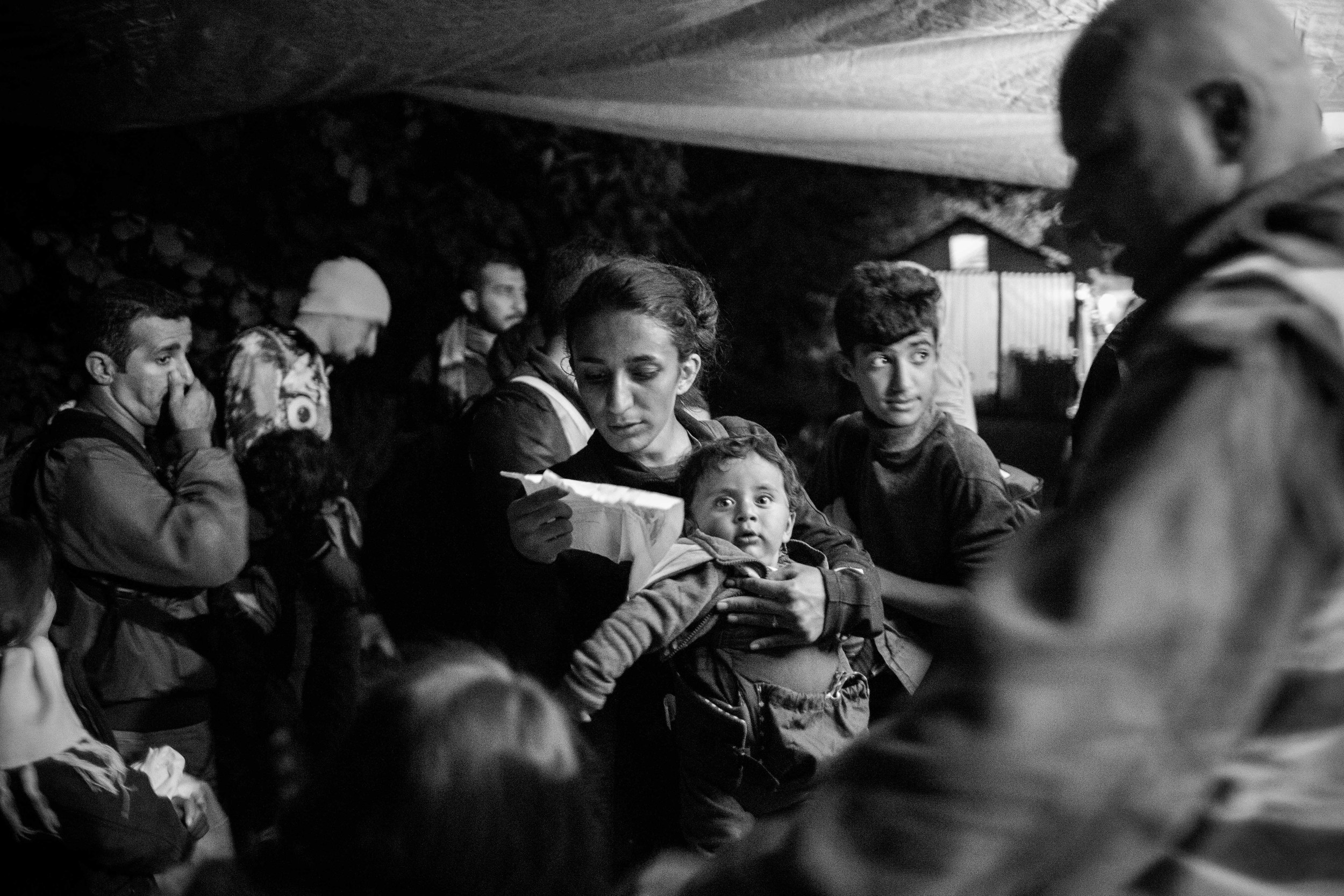 A young Syrian boy with his family about to cross over from Serbia to Croatia in the dead of night.
