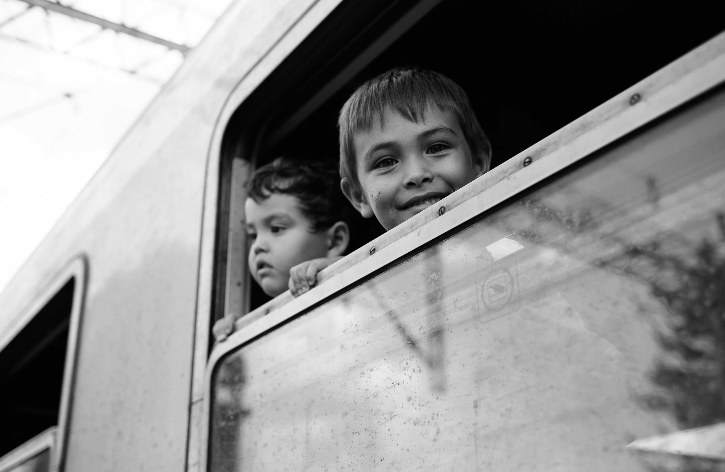 In Tovarnik, Croatia, two young boys peer out of a train that will transport refugees to Austria.