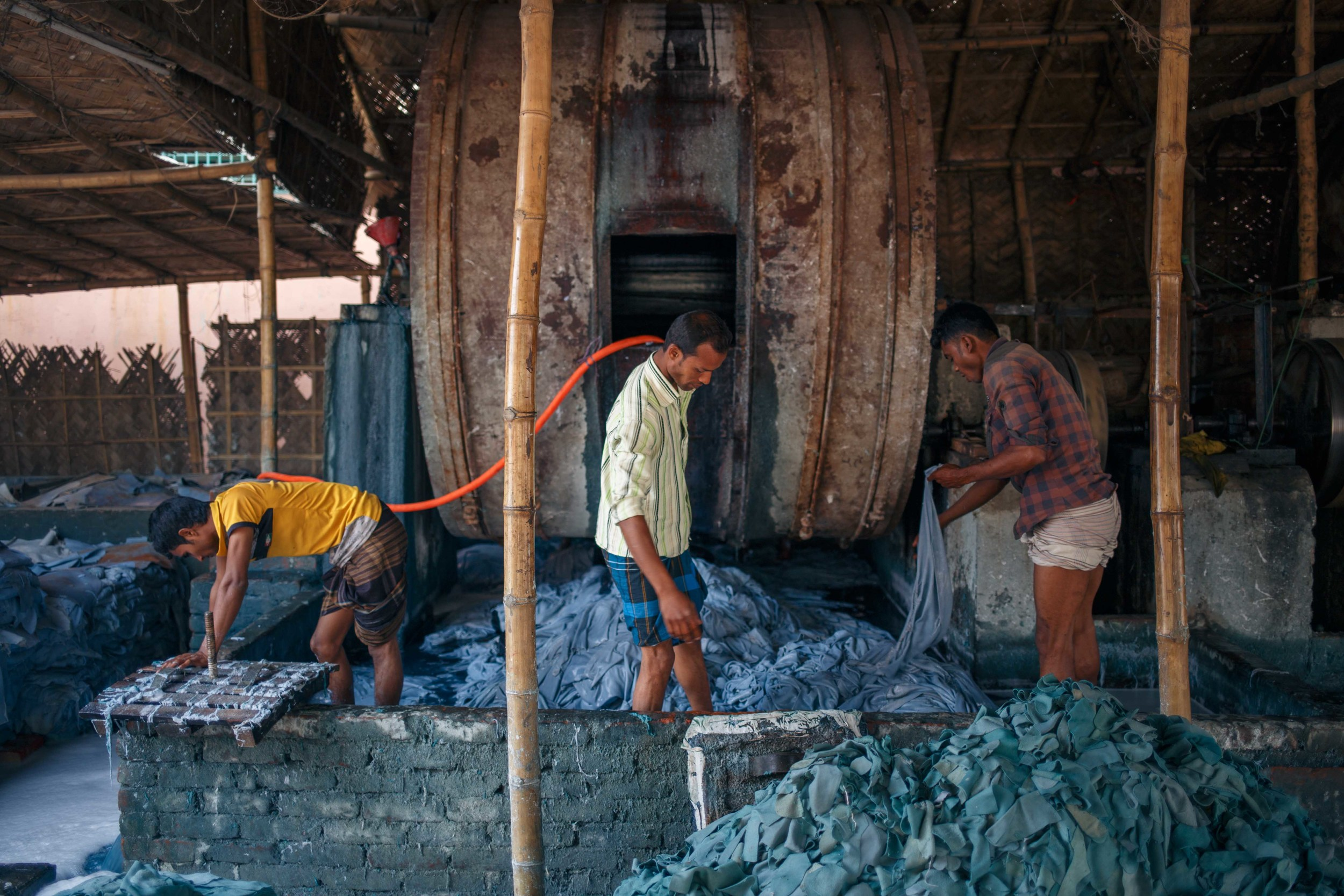 Workers inside a pit for the treatment of leather hides.