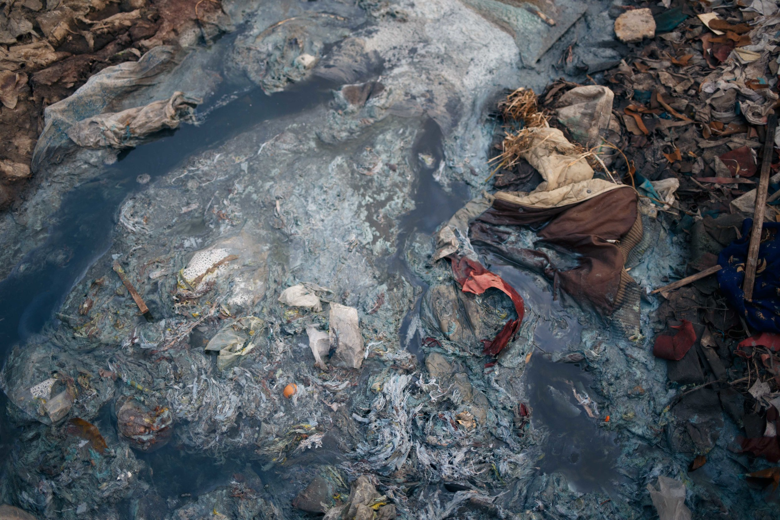 A closer look at the runoff water from the tanneries. Toxic water, plastic, animal and human waste, all flow together into the Buriganga. Residents of Hazaribagh fish in the river and ingest some of the chemicals released by the tanneries elevating their risk of fatal diseases.
