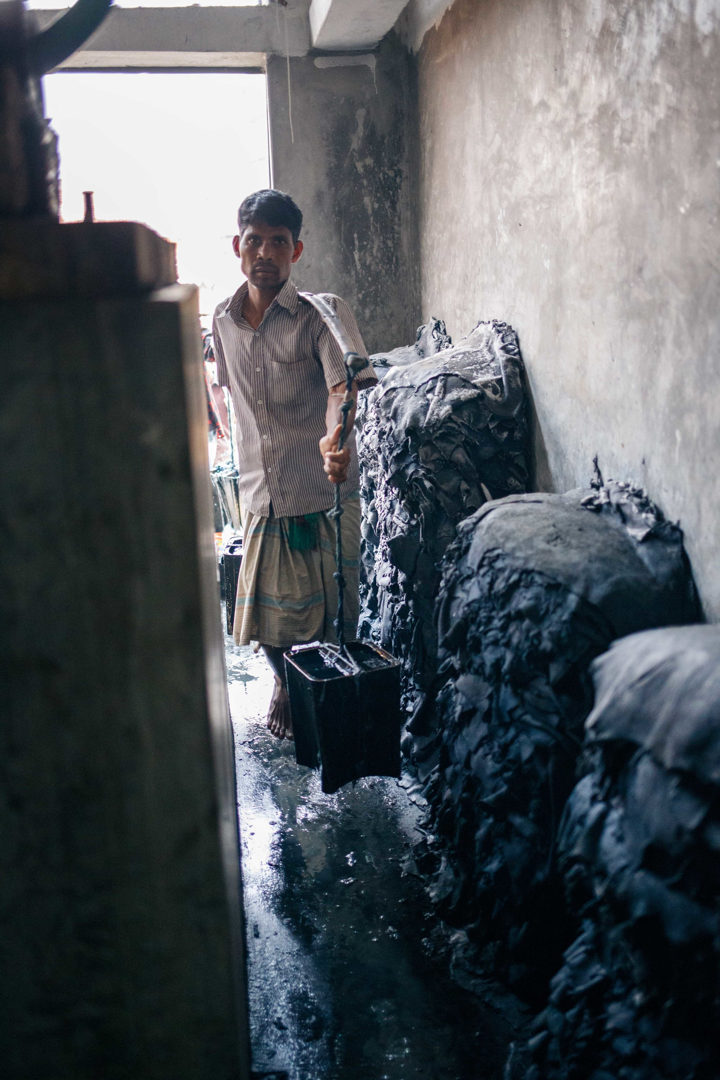 A man carries buckets of acid to dump into the bleaching pits.
