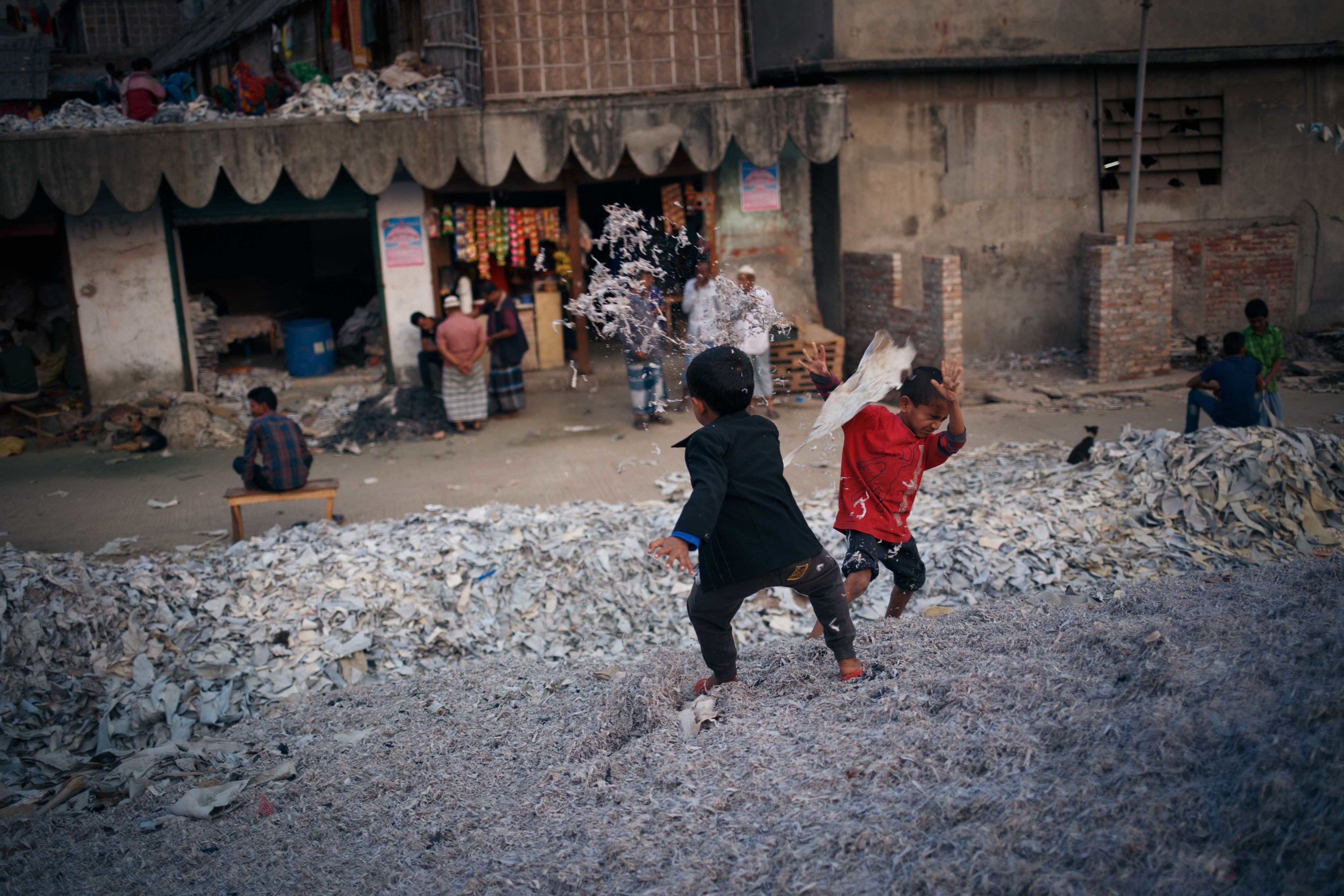 Children play among piles of discarded leather.