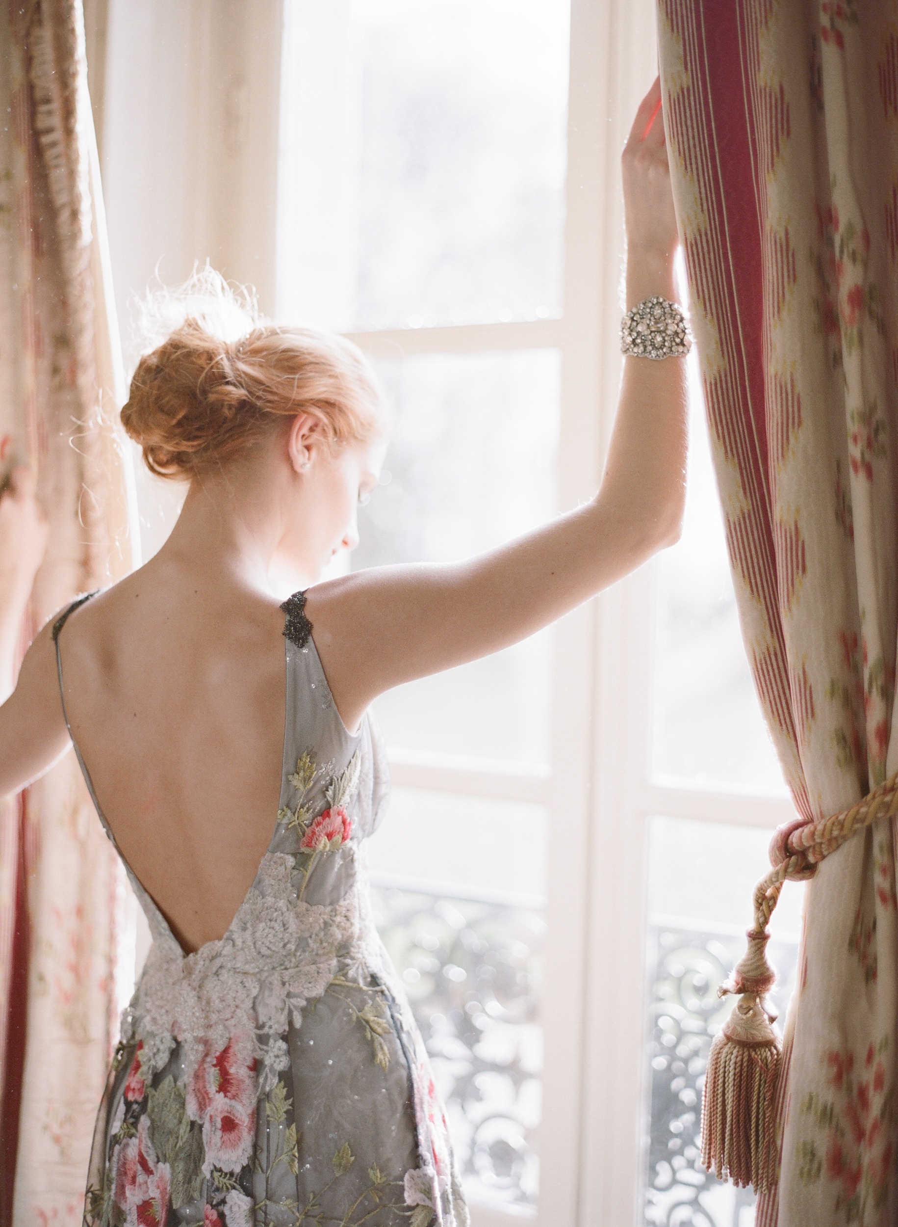 Bride stands at the window in Chateau de Varennes; Sylvie Gil Photography