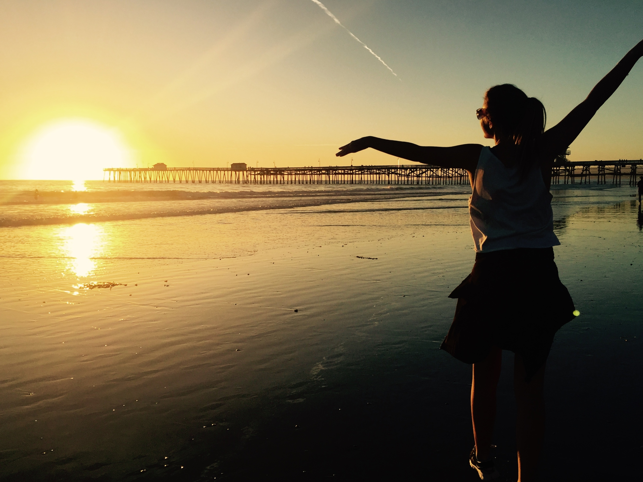 Vague, uplifting picture of me frolicking on the beach at sunset. San Clemente Pier // San Clemente, California.