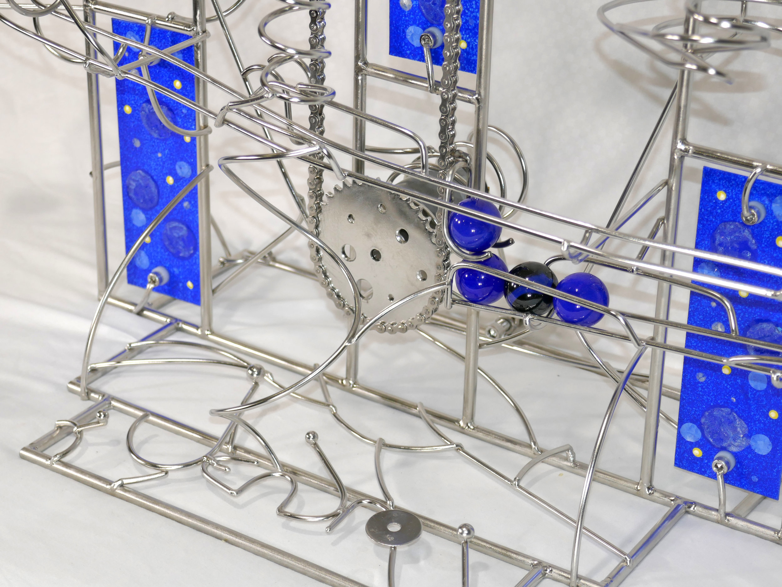Rolling Ball Sculpture - kinetic art works - showing the blue marbles going up the chain lift with artists signature in metal