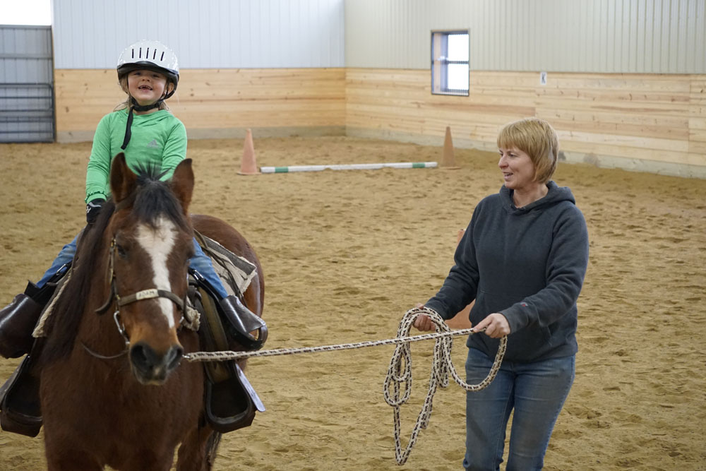 Susan Berger & a student during a private riding lesson in the indoor arena.