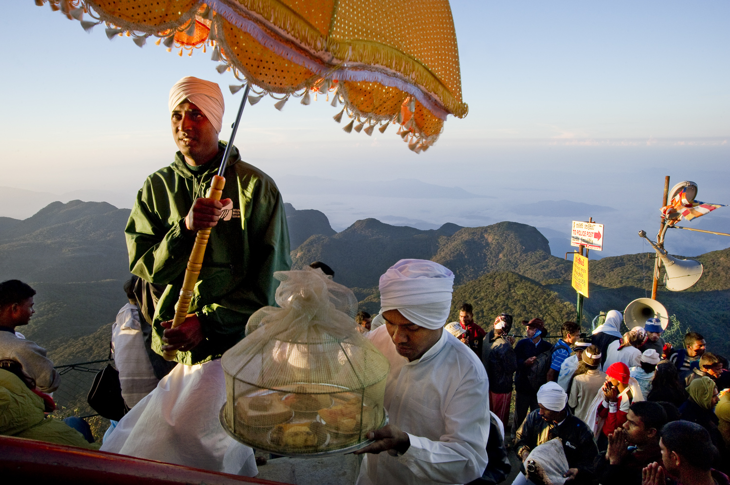 Pilgrims carrying offerings to the top of Adam's peak, a holy site for Sri Lankans of all faiths. While Buddhists believe the rock to be imprinted with the Buddha's footprint, Christians consider the footprint to be of St. Thomas and Muslims see it as Adam's first step outside of paradise. With the rock visible from sea and visited early on by the likes of Marco Polo and Ibn Battuta, the peak has near mythic status for Sri Lankans.