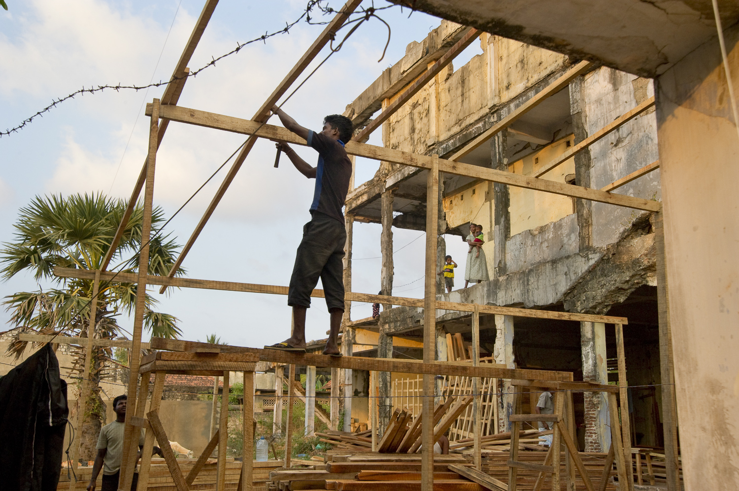 Near downtown Jaffna, locals construct a wood-shed in the remnants of war-destroyed housing. As new building materials are imported from the south, Jaffna is showing signs of development and new investments.