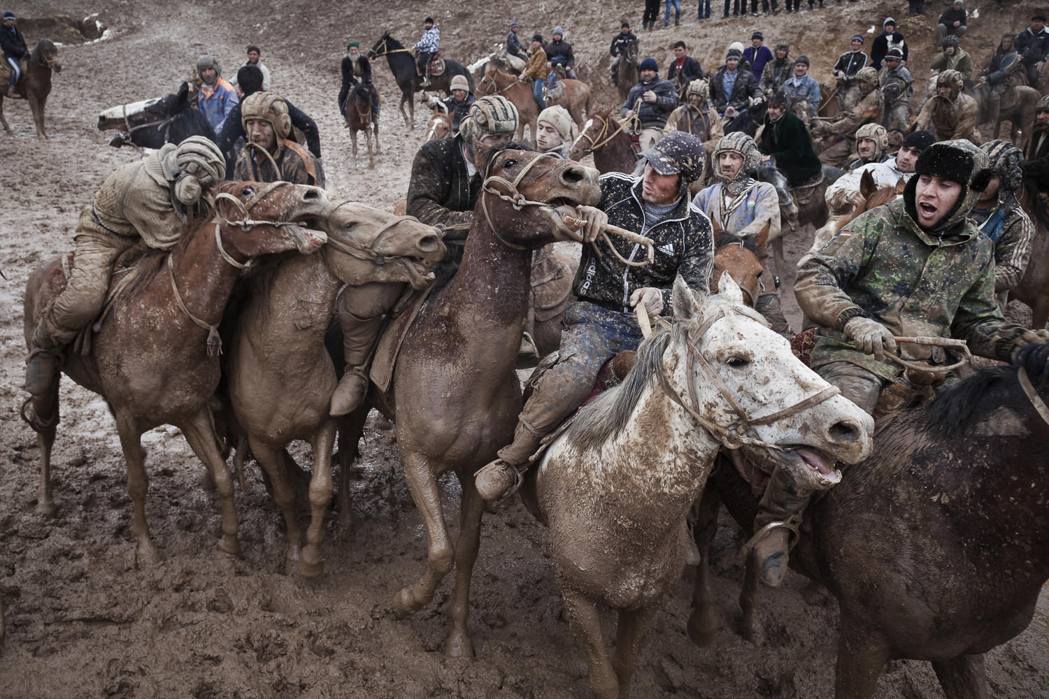 Buzkashi players fight for possession for the buz during a muddy match in Nojibolo, western Tajikistan.