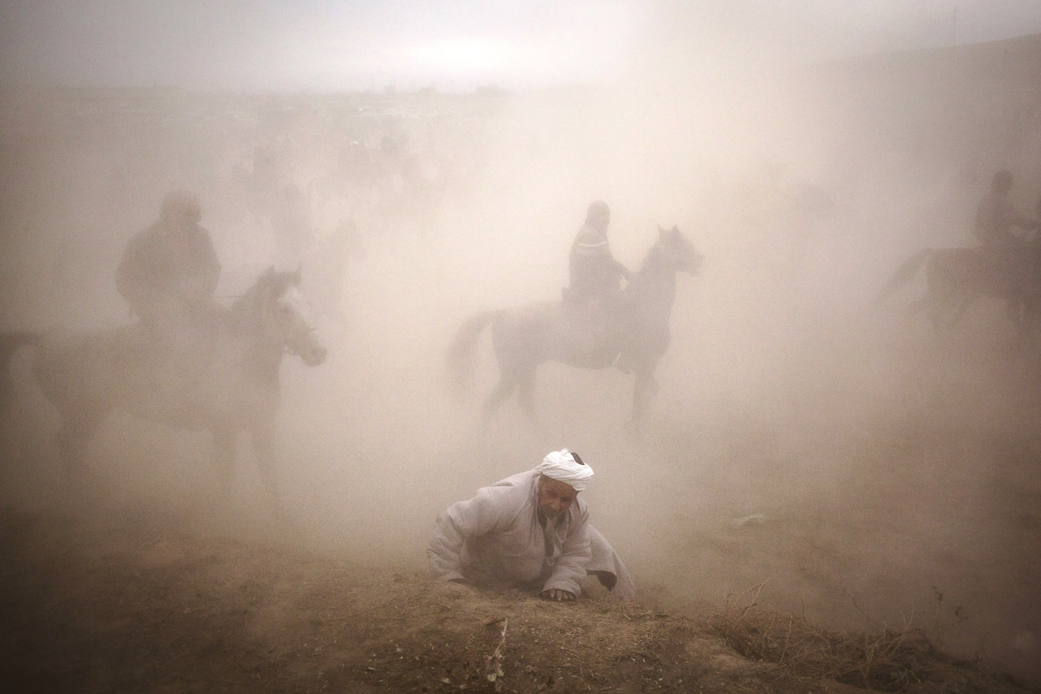 Too slow to jump to a retreat with the rest of the audience, an old man is lost in the dust of a horde of buzkashi horses. Near Sharinav, Tajikistan. Popular throughout much of Central Asia, buzkashi is a form of horse polo in which horseback players wrestle a goat carcass across a playing field.