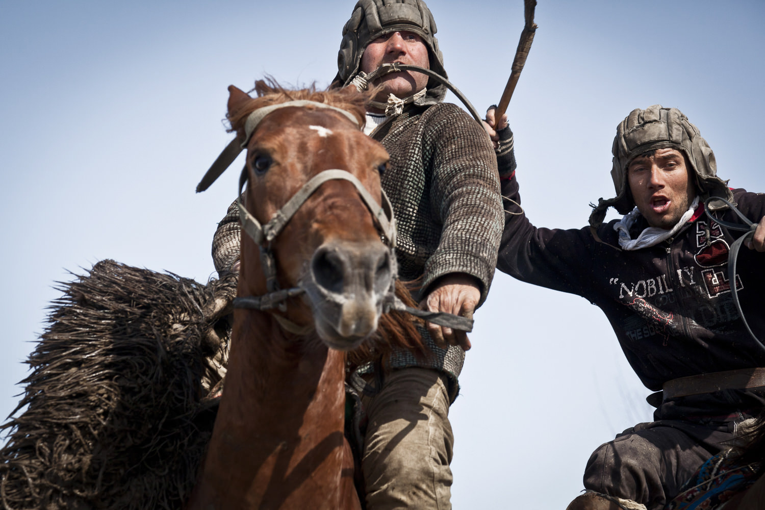 A buzkashi rider escapes from a rival with the prize.  Popular throughout much of Central Asia, buzkashi is a form of horse polo in which horseback players wrestle a goat carcass across a playing field.