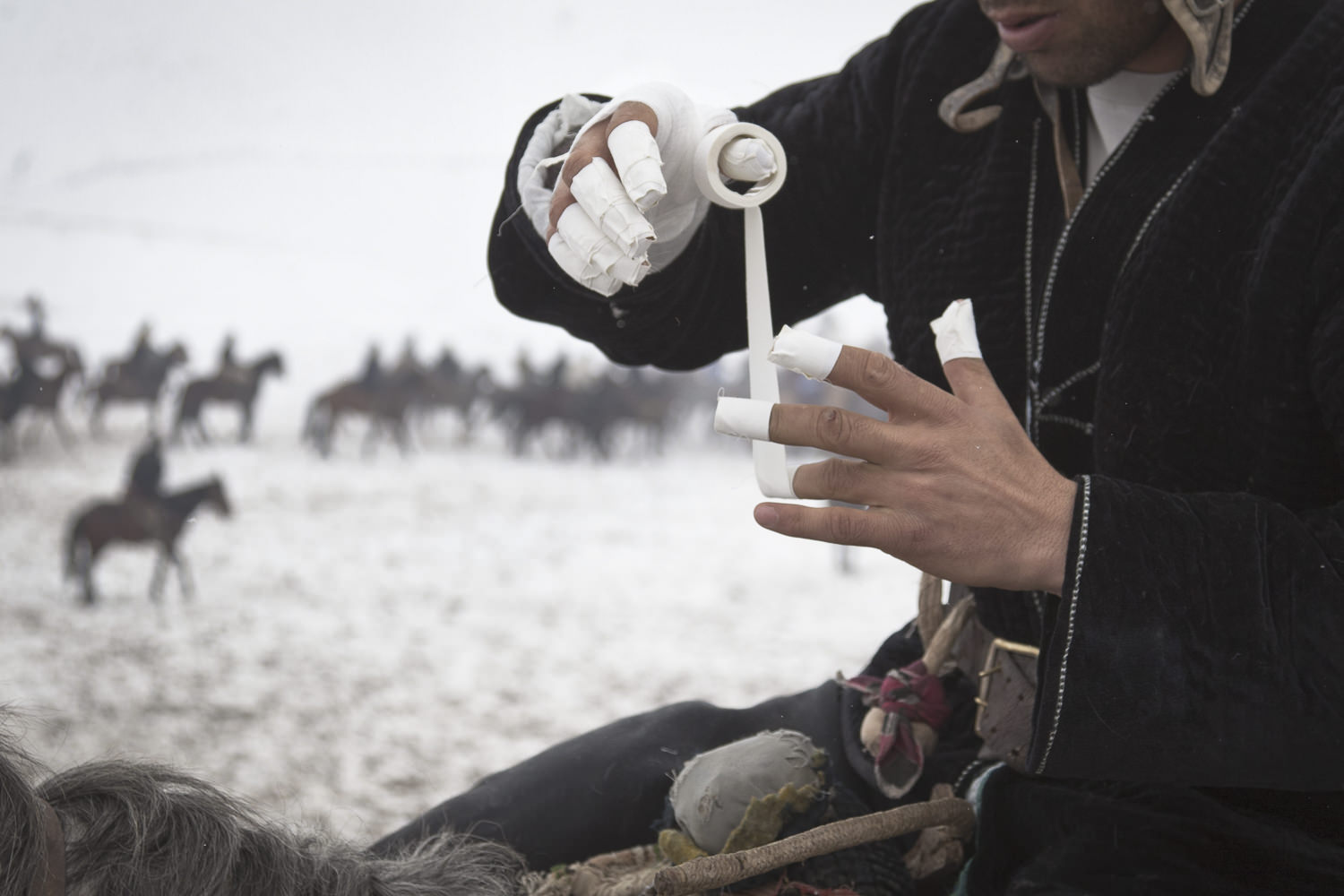 Between rounds, a buzkashi rider tapes up his hands to improve his grip, stave off the cold and ward off brutal whips from other players. Popular throughout much of Central Asia, buzkashi is a form of horse polo in which horseback players wrestle a goat carcass across a playing field.