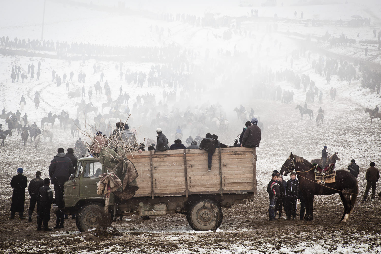 Spectators rally around a snowy buzkashi field. The truck in the foreground is both the prize truck, the announcer's truck and the holding pen for goats (buz) for the game.
