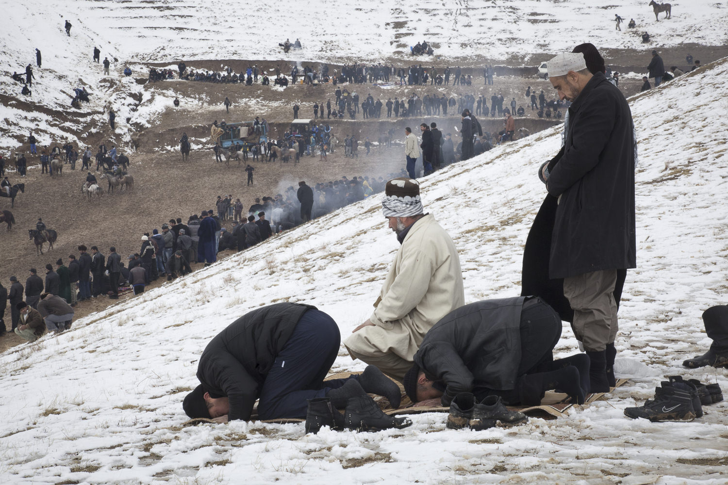 Using carpets won by the horseback riders, buzkashi fans near Hissor set aside time for afternoon prayers.