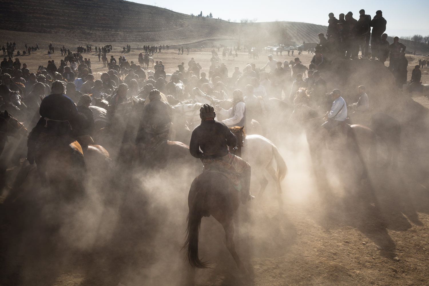 Sunlight and dust streams around Buzkashi players in Sharinav, Tajikistan. Spectators stand on a mound nearby - audience members often wander as close as possible to watch the game.
