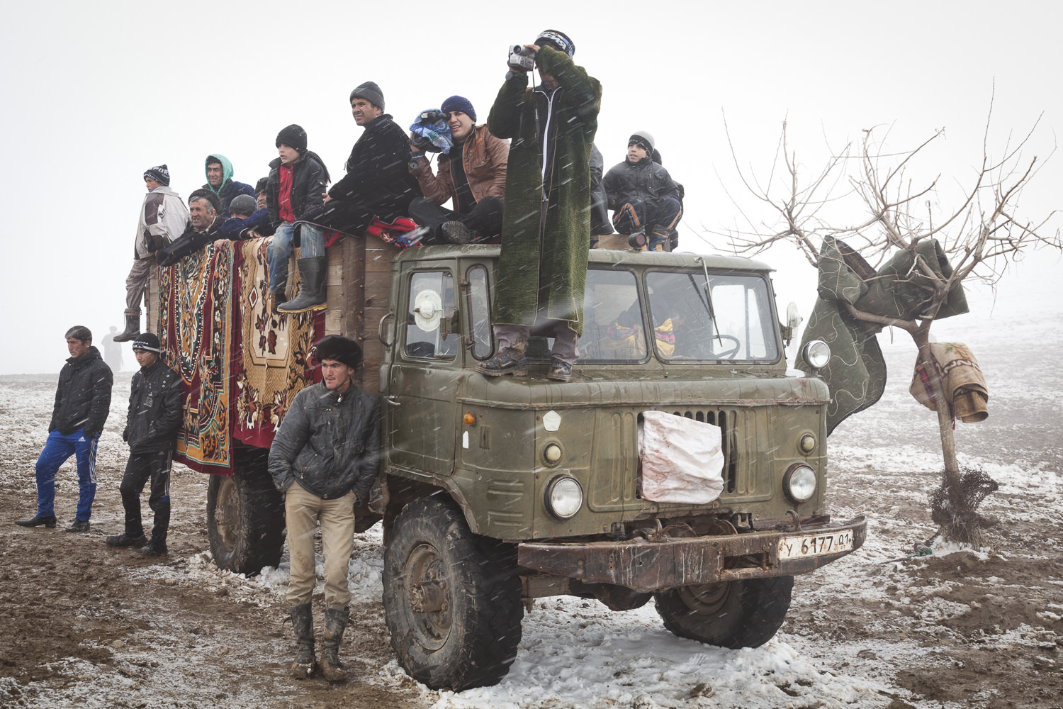 Buzkashi fans cluster around a truck holding competition prizes.