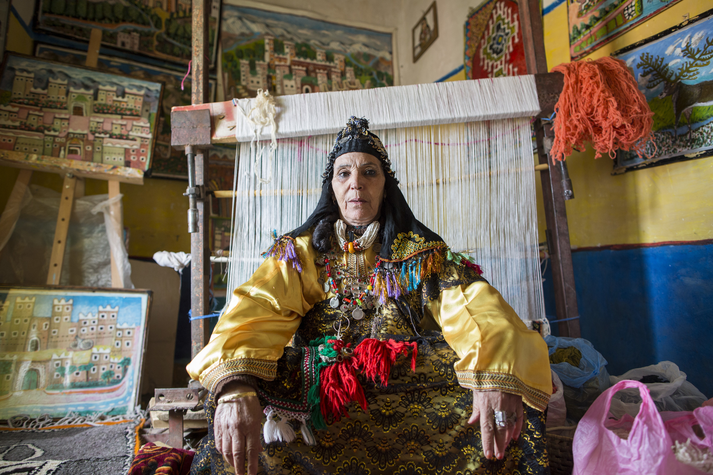 """Fadma Aid Hemam, 63, in her traditional clothing, sits in her home studio surrounded by her artwork and carpets, """"Amazigh is my identity. I wouldn't change that for anything in the world."""""""