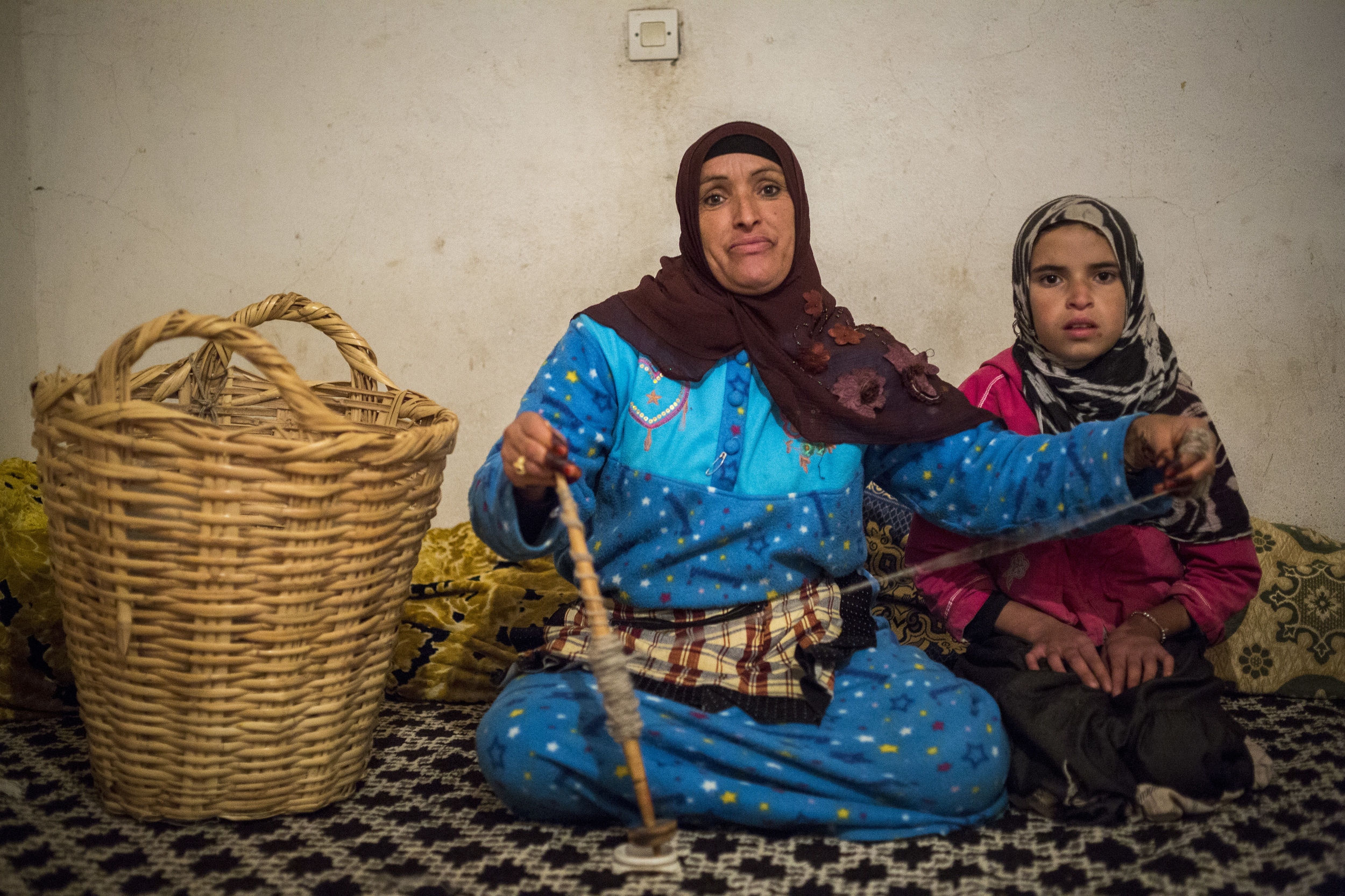 """Zayna Jawab, 38, spins wool while in her living room with Fatima Afker, 12, """"I wish for my daughter to grow up and never forget her heritage. I pray she lives in the principles I taught her."""""""