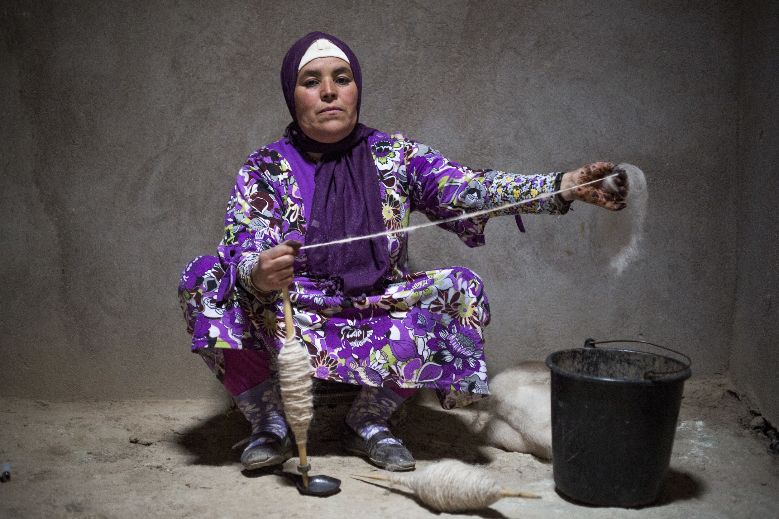 "Rkia Bourraht, 44, sits on a small pillow while spinning, a common task among women in the village, ""We have everything we need in here, and we do everything by ourselves. We are too proud to ask people outside to help."""