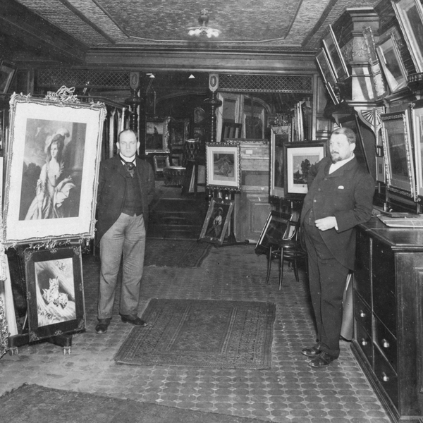 Black and white photo of Charles and John Kraushaar in front of framed art