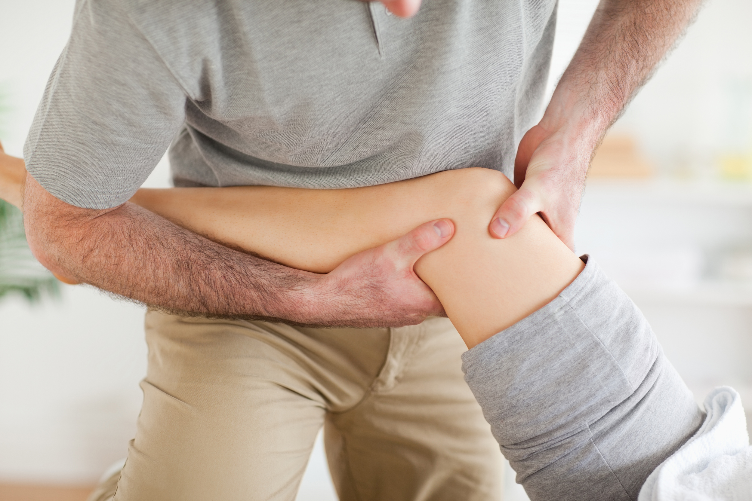 doctor helps patient with injury therapy
