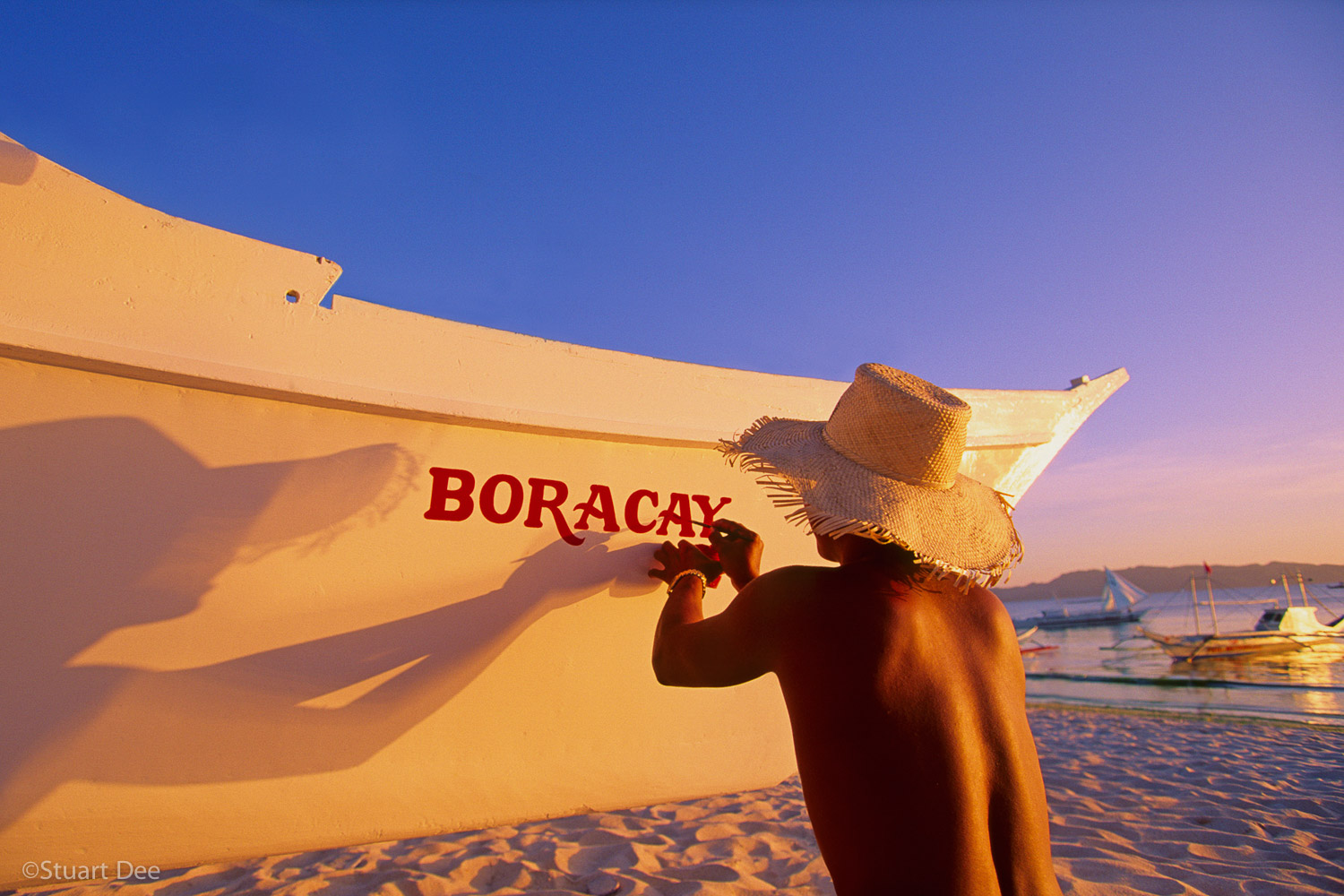 Man painting name on boat at beach, with tranlucent shadow, Boracay, Panay, Philippines