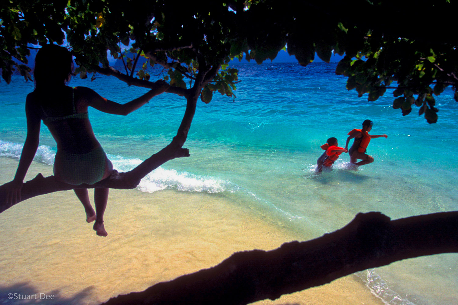Woman watching two children playing on a beach, Entalula Island, El Nido, Palawan, Philippines