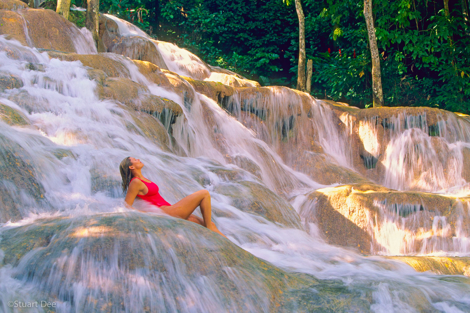 Woman relaxing at falls, Dunn's River Falls, Ocho Rios, Jamaica. Dunn's River Falls is the most visited tourist site in the Carribbean.  R