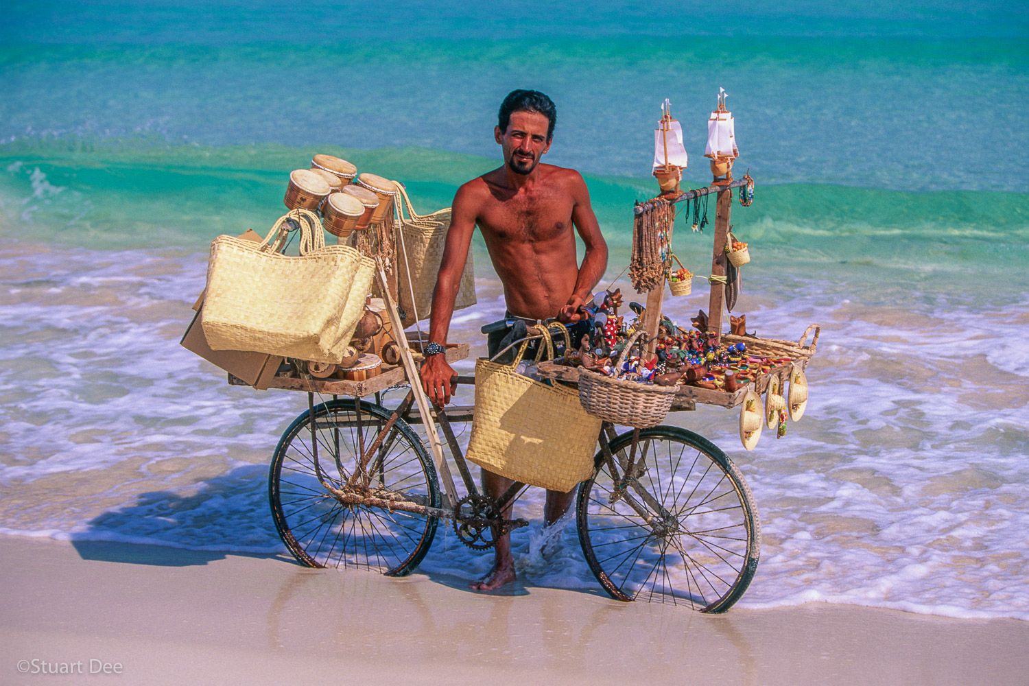 Beach vendor selling souvenirs, with his bicycle, Varadero, Cuba  