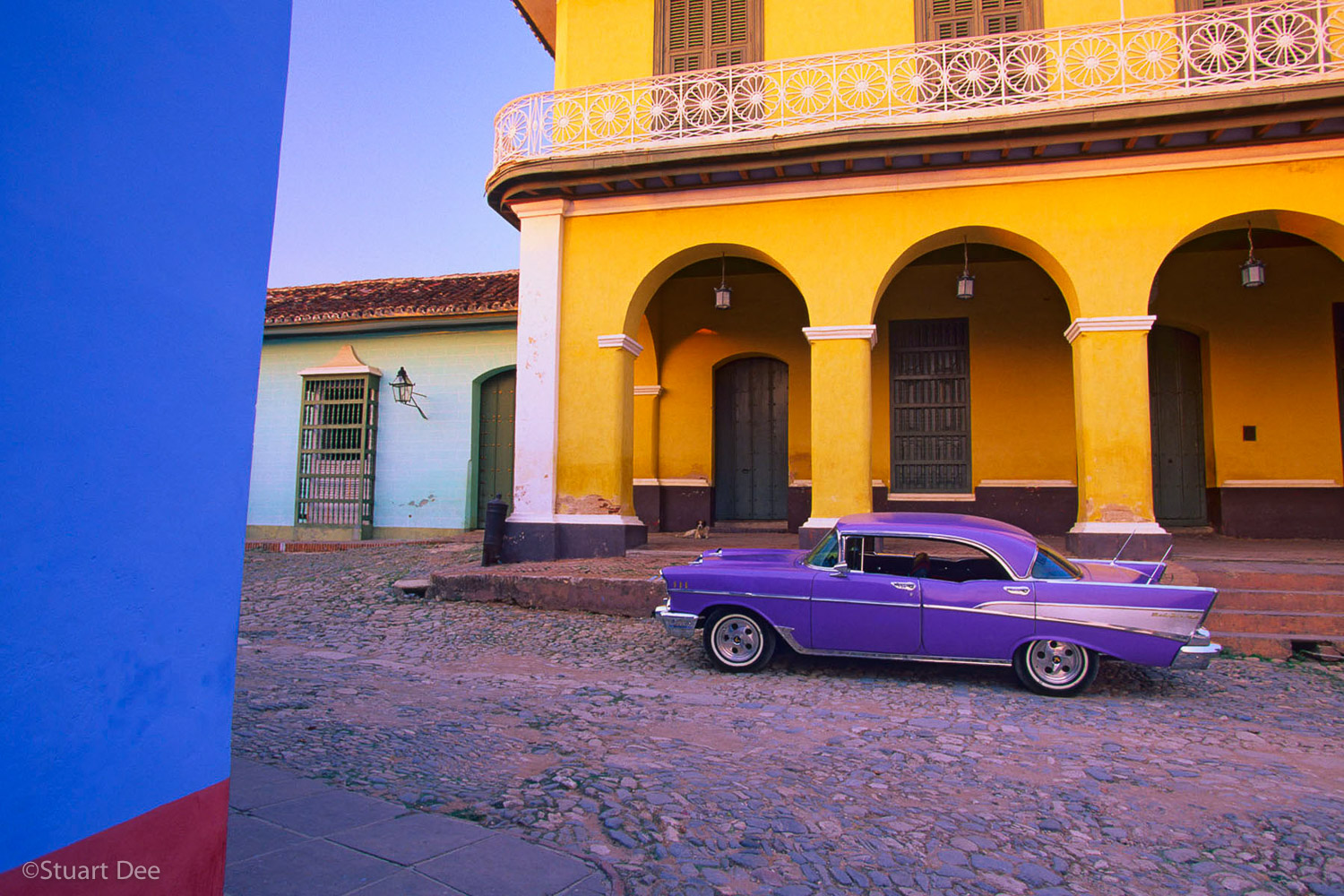 A purple 1957 Chevrolet Bel Air hardtop on a street with colorful facades, in Trinidad, Cuba.