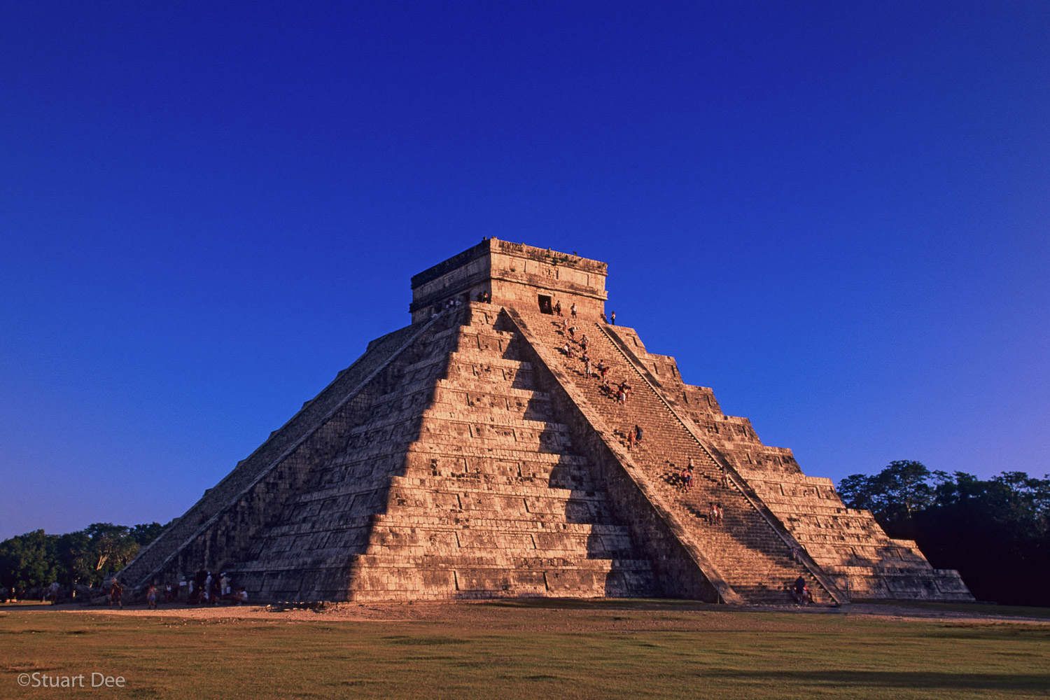 Mayan Pyramid of Kukulkan, (El Castillo or The Castle) at sunset, with some tourists climbing to the top, Chichen Itza, Mexico