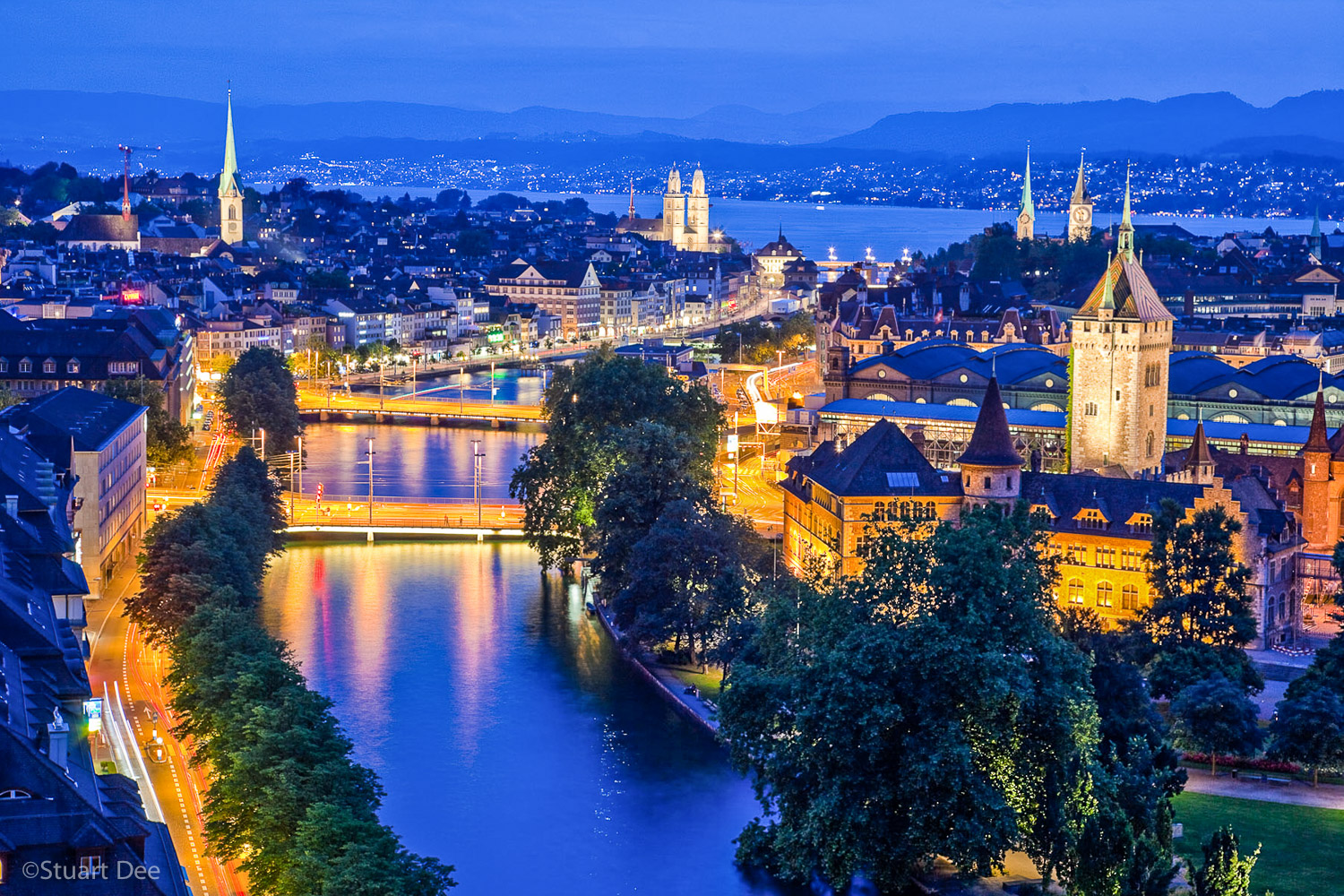 Aerial view of city skyline at dusk/night, Zurich, Switzerland. This view shows the Limmat River and Lake Zurich, and the spires of the most prominent churches. Zurich is the largest city in Switzerland, and is its commercial, banking, and cultural center.