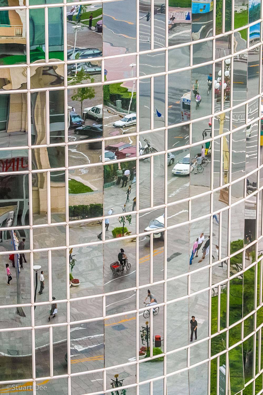 Kaleidoscope of street activity reflected in building, Beijing, China