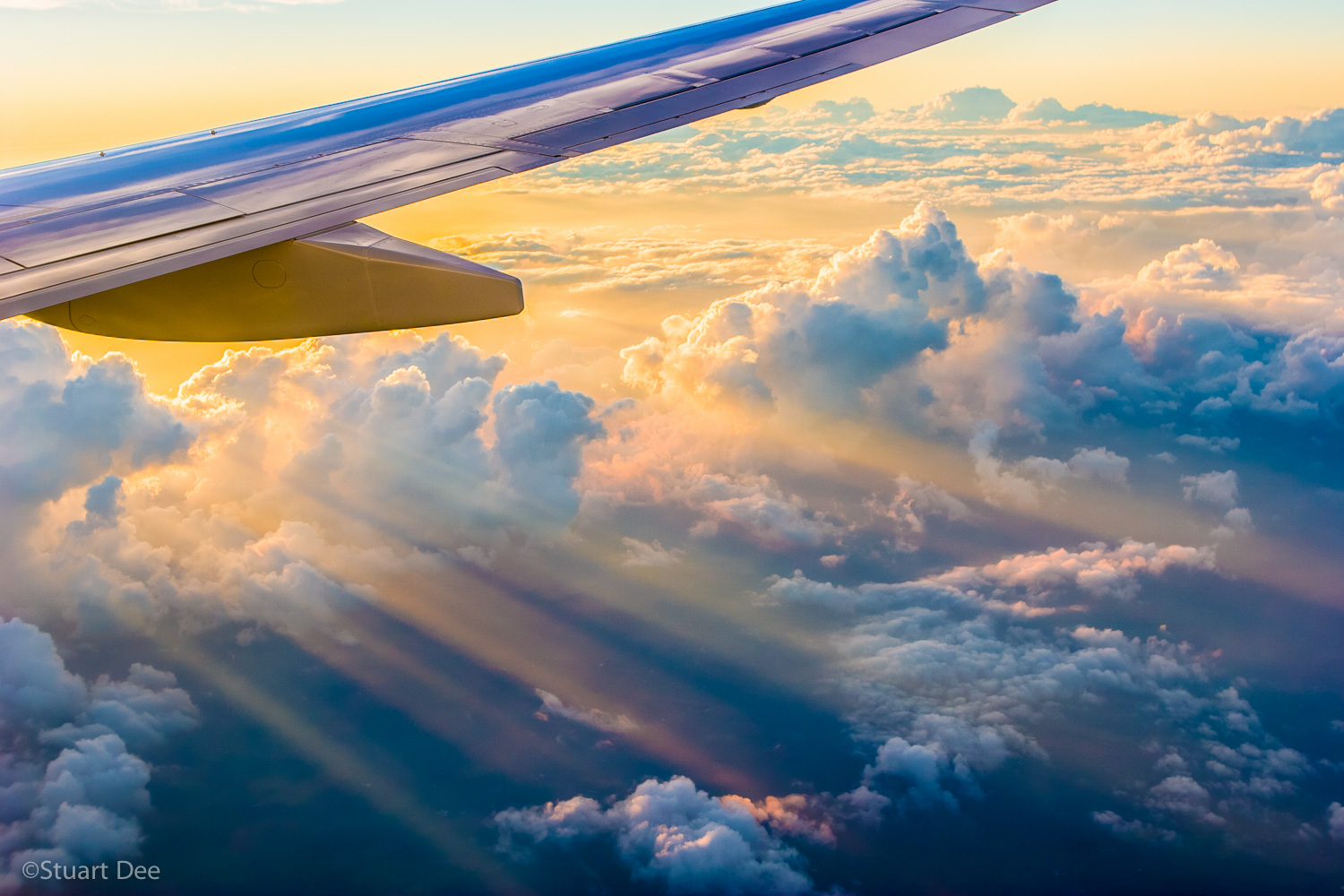 Airplane wing against dramatic clouds with sun's rays