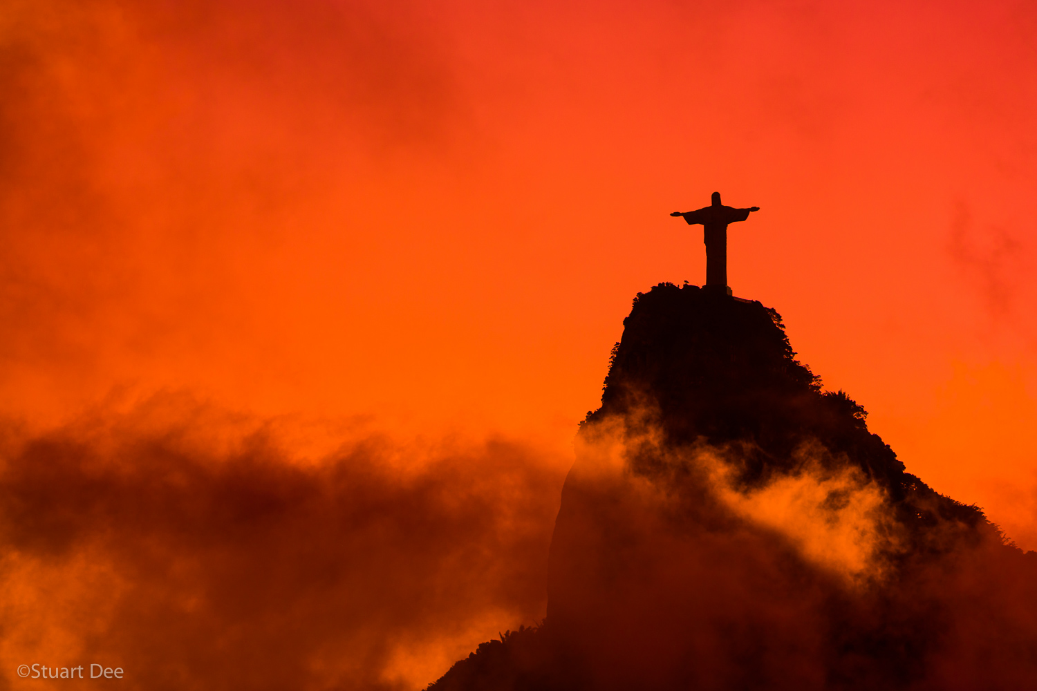 Christ the Redeemer statue, (Cristo Redentor), at sunset, with misty clouds, atop Corcovado, Rio de Janeiro, Brazil. This statue is one of the most well-known symbols of Rio.