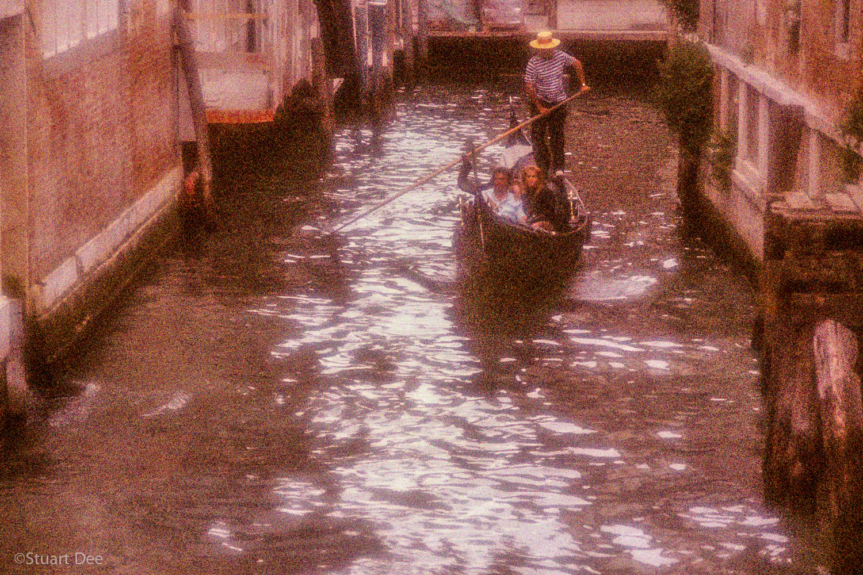 Romantic couple in gondola, Venice, Italy. Grainy, pointiliistic effect, soft focus style.